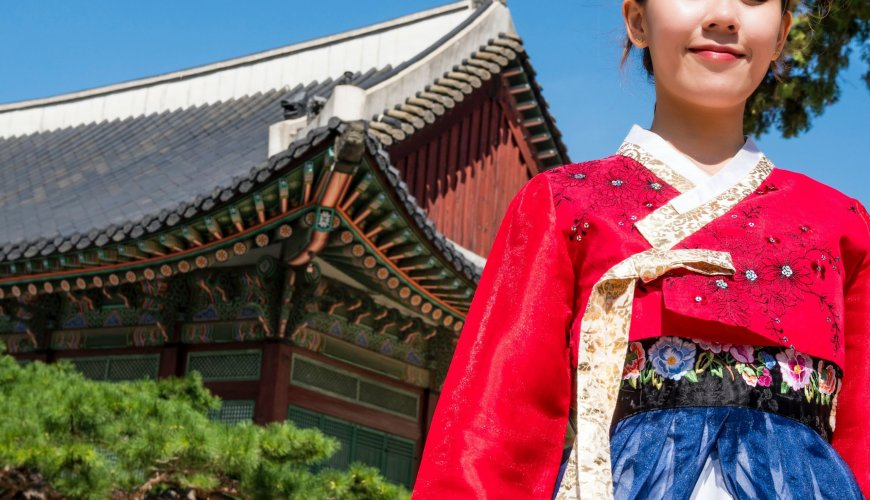 Korean girl in Korean traditional dress smiling in front of Korean traditional house, an image full of culture